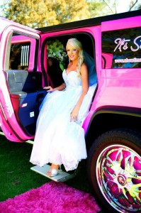 Image of a stunning bride on her wedding day as she is chauffeured through Perth in the pink hummer wedding limousine.